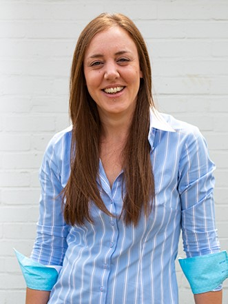 Photo of Jo Pickering, Kabo Creative's graphic designer, smiling in front of a white brick wall