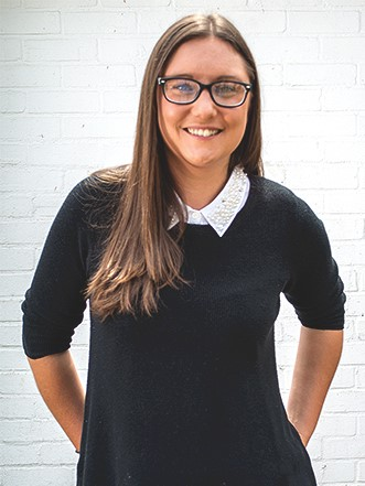 Photo of Penni Pickering, Kabo Creative's website designer, smiling in front of a white brick wall